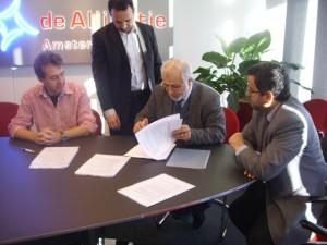 Ahmed al-Rawi tekent een document met achter hem Yahia Bouyafa. Links Alliantie-vertegenwoordiger Bats, rechts Bouabdallah van Europe Trust