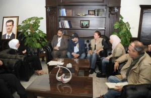 Ruzie over actie Help Syrië De Winter Door. Tegenstanders publiceerden een foto waarin Amin Abou Rashed slechts door een plant van het portret van Assad wordt gescheiden.