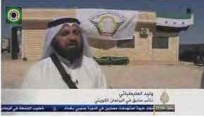 Screenshot van Al-Jazeera-interview met Al-Tabtabae met Liwa Al-Tawhid vlag op de achtergrond.